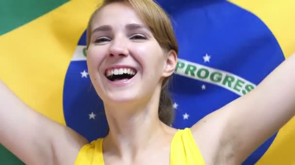 Brazilian Young Woman Celebrating while holding the flag of Brazil in Slow Motion
