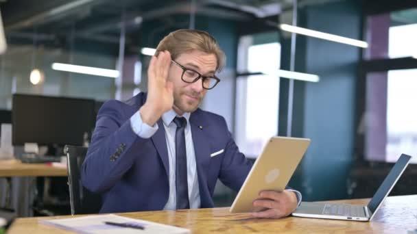 Geschäftsmann spricht für Video-Chat auf Tablet