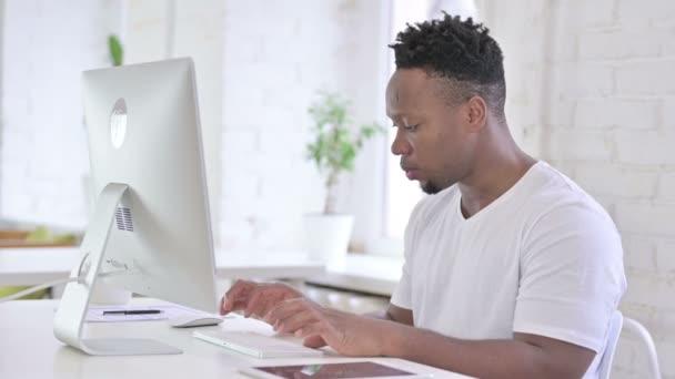 ambitionierter lässiger Afrikaner feiert Erfolg auf dem Desktop