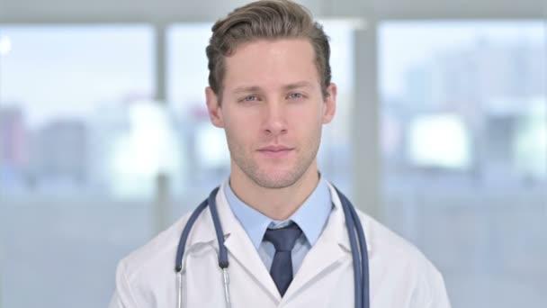 Portrét mladého mužského doktora ukazující palce v kanceláři