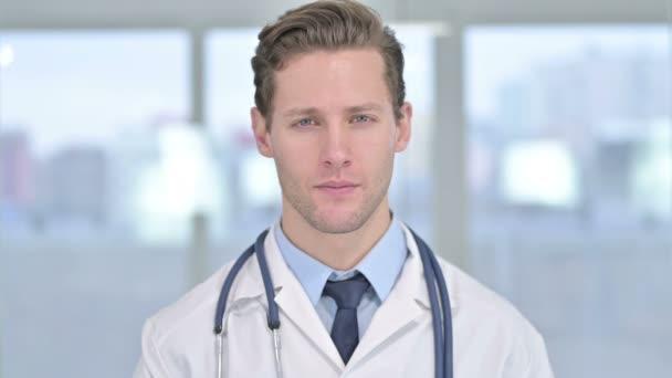 Porträt eines lächelnden jungen männlichen Arztes, der in die Kamera blickt