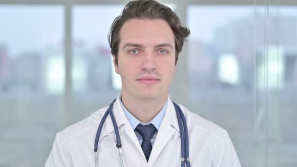 Porträt eines lächelnden jungen Arztes, der in die Kamera blickt