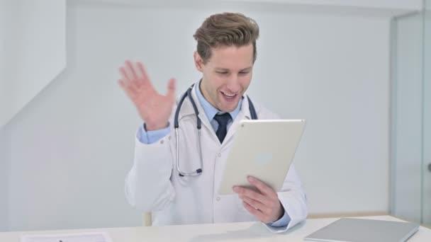 junger männlicher Arzt macht Video-Chat auf Tablet im Büro