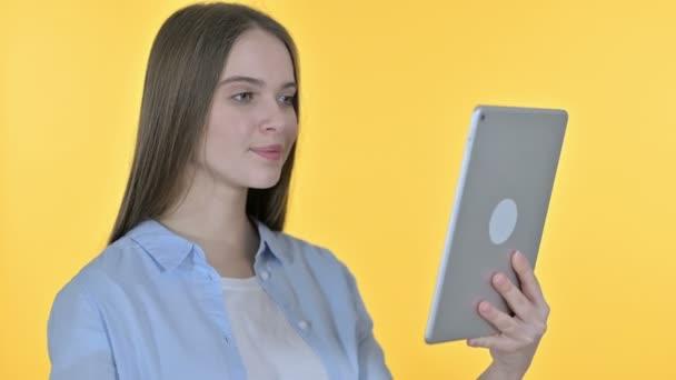 Video-Chat auf dem Tablet von junger Frau, gelber Hintergrund