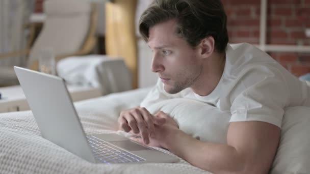 Ambiciózní mladý muž pomocí notebooku v posteli