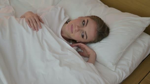 Vonzó fiatal nő próbál aludni az ágyban