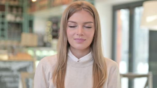Porträt einer jungen Frau, die in die Kamera winkt