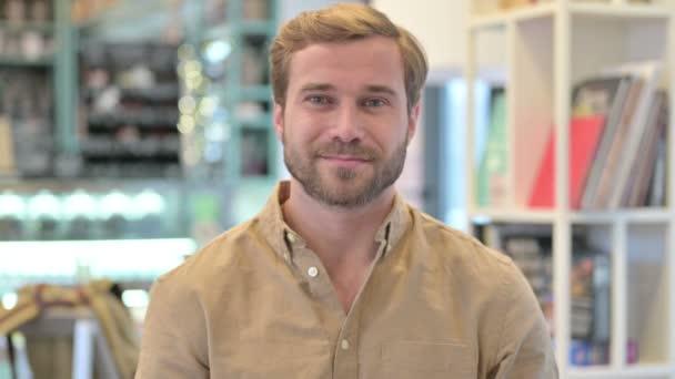 Portrét atraktivního mladého muže usmívajícího se na fotoaparát