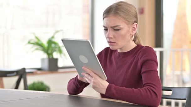 Misserfolg: Junge Frau mit Verlust auf Tablet im Büro