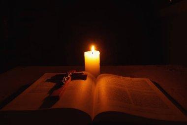 Yanan mum, İncil ve haç üstünde okul sırası