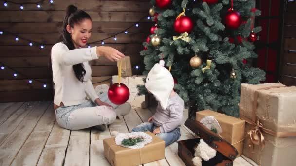 Mutter und entzückende Baby Playying an Weihnachten