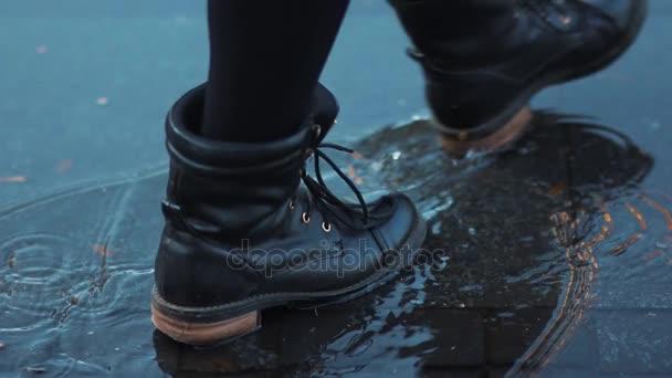 nohy v botách přes podzimní louže