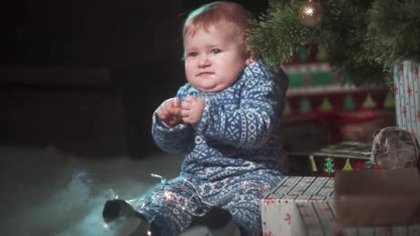 Baby Boy in der Nähe von Weihnachtsbaum mit Geschenken