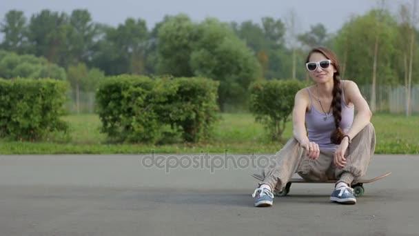 mladá žena pózuje s skateboard