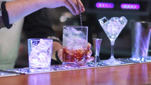 bartender mixing whiskey and ice at bar