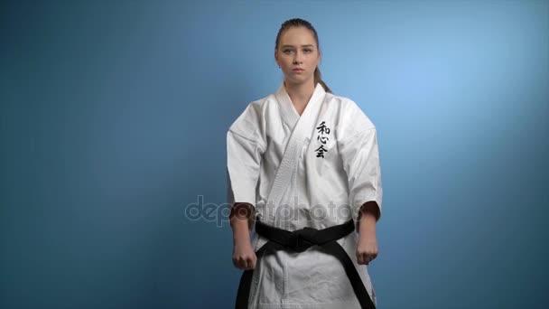 Žena v karate pozdrav pozice izolované na modré