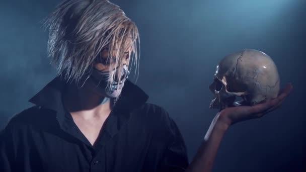 Zlý muž s halloween make-upu a lebky