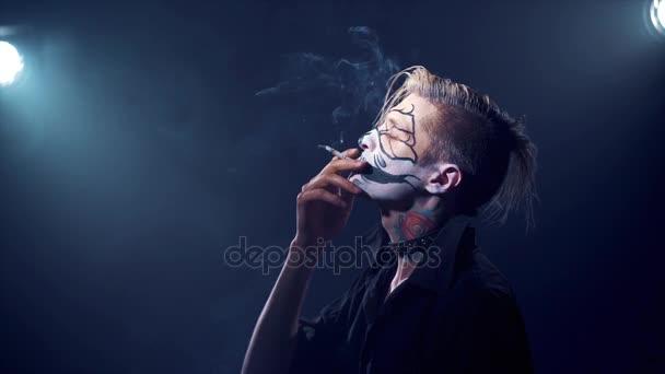 man with halloween makeup smoking