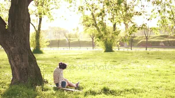 Hübsche Mädchen im Freien sitzen unter dem Baum