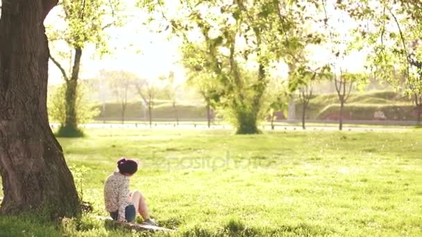 Krása žena venku sedí pod stromem