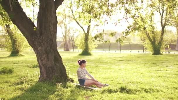Krásy dívka, sedící pod stromem