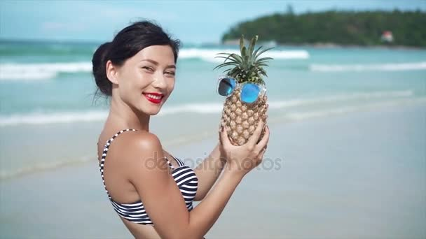 Woman having fun with a pineapple in sunglasses