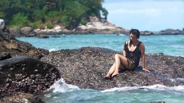 Hot žena sedící na skále v moři