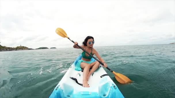 01b2bf65d0 Young pretty woman in sunglasses rowing in a kayak — Stock Video ...