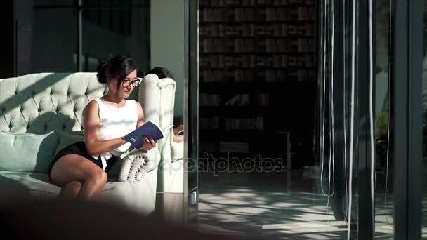 Dívka se odpočinku na gauči a drží knihu
