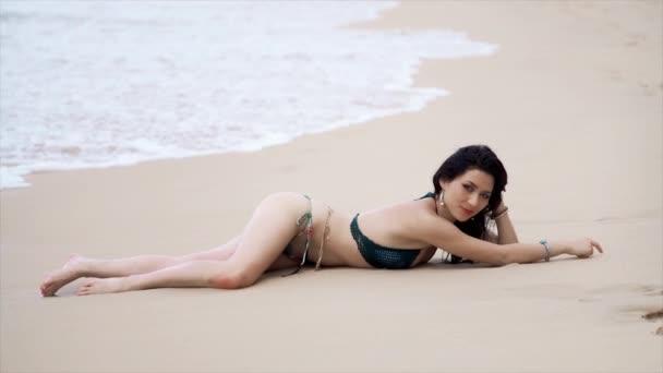 Szexi lány pózol a tenger hullámai szexuális fürdőruha
