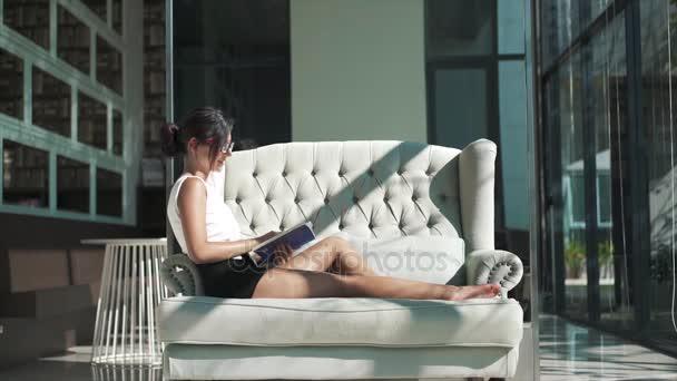 Šťastná žena odpočinku na pohovce a čte knihu