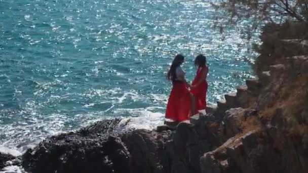 Girls in red dresses together at ocean cliff beach