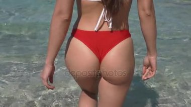 Beautiful young woman buttocks walking to the sea