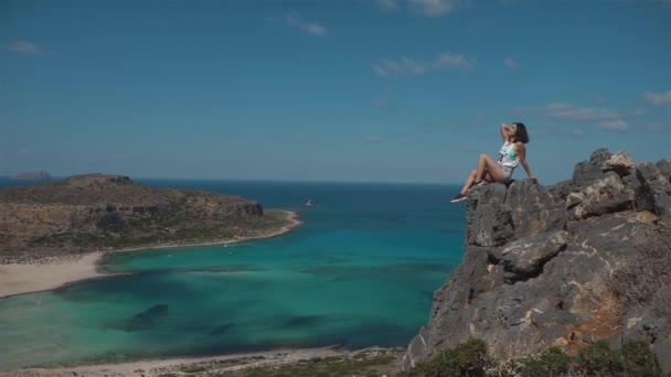 Happy woman standing on the cliff of mountain