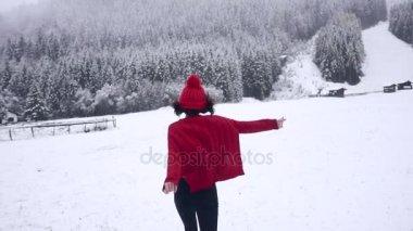 Happy girl running in snowfall in slow motion