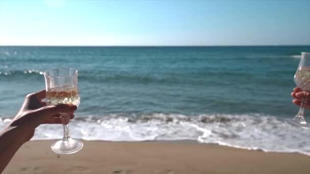 Cheers mit Weißweingläser in einem Strand