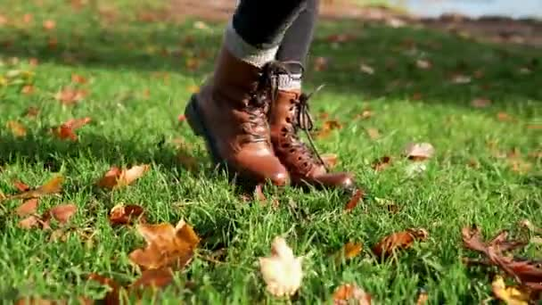 woman legs walking on autumn leaves