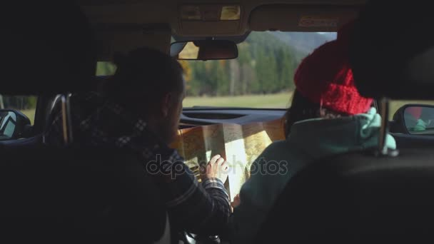 Happy couple sitting in car with a map