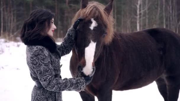 gyönyörű lány etetés a téli erdő a lovas