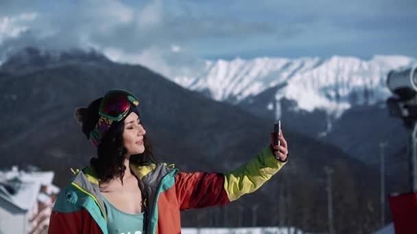 Snowboardista žena dělat selfie na telefonu