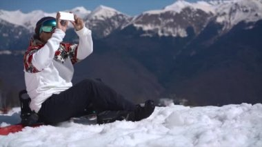 Snowboarder photographing in the mountains