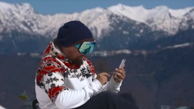 Snowboarder using mobile phone in the mountains