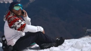 Snowboarder calls to someone in the mountains