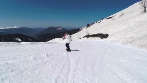 Snowboarder rutscht in Bergen ab, rosa khutor