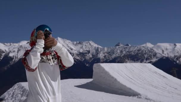 Ein junger Mann filmt Snowboarder mit Action-Kamera