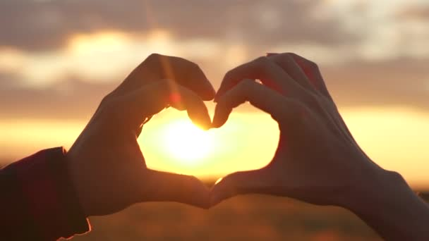 Hands of woman and man made a heart shape at sunset, on the abstract background, against an orange field, ocean or sky. Concept or sign of love to relax at sea, freedom, life style, silhouette, nature