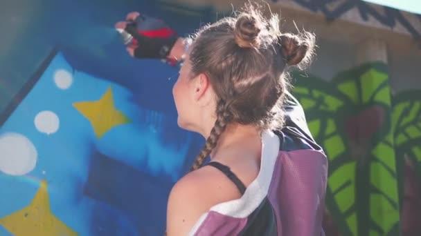 Talentovaná hipsterka kreslí obrázky. Krásná mladá dívka dělá barevné graffiti s aerosolovým sprejem na městské ulici zdi v létě. Kreativní umění. Svoboda, životní styl, kulturní koncepce.
