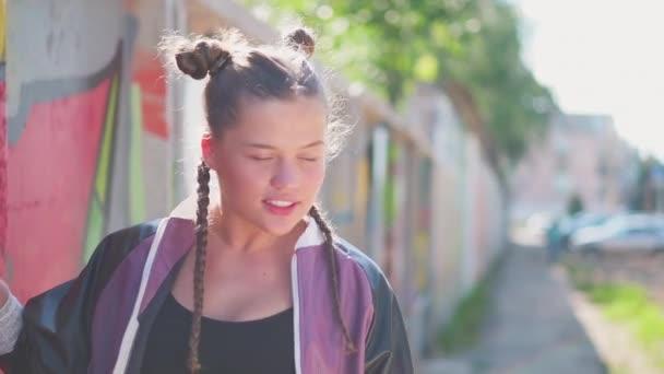 Svoboda, životní styl, kulturní koncept. Krásná mladá dívka dělá barevné graffiti s aerosolovým sprejem na městské ulici zdi v létě. Kreativní umění. Talentovaná hipsterka kreslí obrázek.