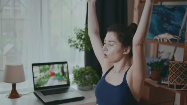 Fiatal nő sportolni otthon néz internetes leckét, Női fitness edzés sportruházat a nappaliban laptoppal. Egészséges életmód a karantén alatt. Pandémia és kovid fogalom.