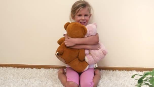 Pěkně s úsměvem dívka objímá plyšových medvědů v herně